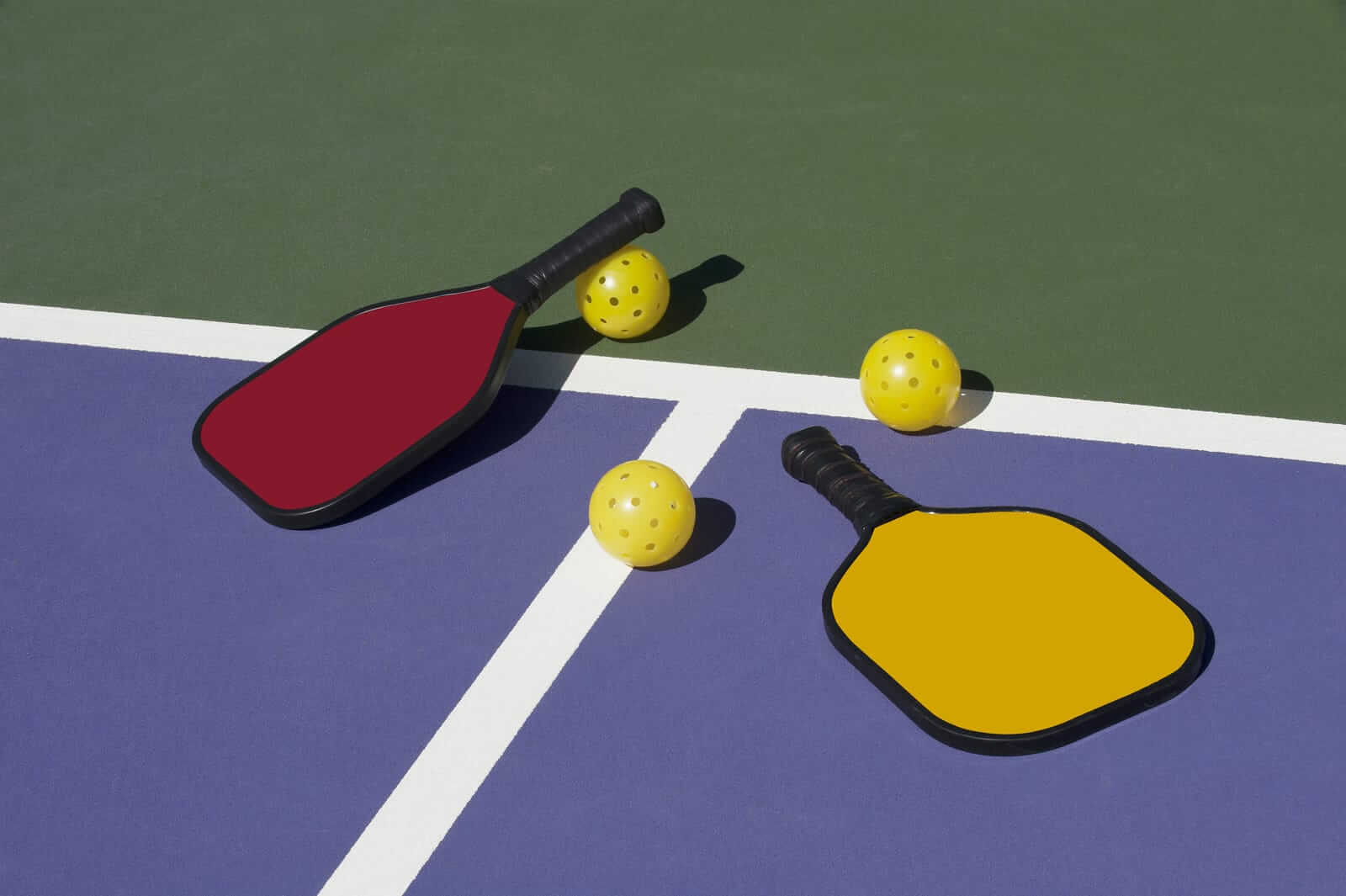 Pickleball Paddles And Balls On The Court
